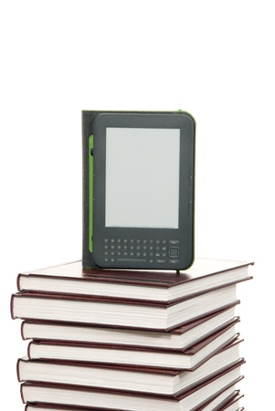 e ink: Kindle Wireless Reading digital book Device, Wi-Fi tablet pad, Graphite, 6 Display with New E Ink Pearl Technology over stack of books Stock Photo