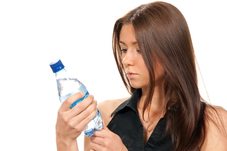 still water: Woman reading lable bottle of pure still drinking water nutrition facts. Female hold in hand sparkling mineral bottled water isolated on a white background. Healthy lifestyle concept