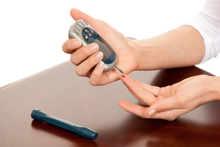 Dependent first type Diabetic patient measuring glucose level blood test using smart mini glucometer and small drop of blood from finger and test strips isolated on a white background photo