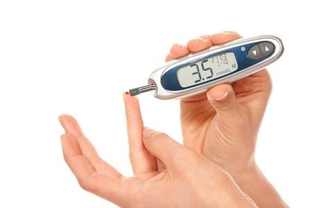 Diabetes medida paciente glucosa nivel examen de sangre con ultra glucómetro mini y pequeña gota de sangre de tiras de dedo y prueba aislado en un fondo blanco. Hipoglucemia Foto de archivo
