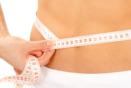 Athletic fit slim woman measuring her waist metric tape measure around after a diet  isolated over white background photo