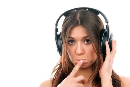 Attractive cheerful brunette woman listening and enjoying music in headphones, one hand finger touch mouth isolated on a white background photo