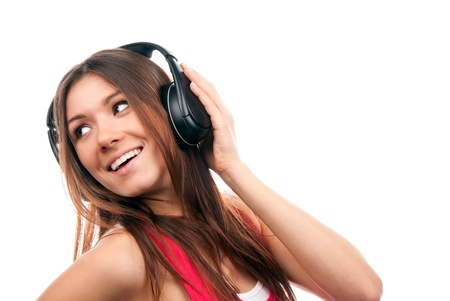 Attractive cheerful brunette woman listening and enjoying music in headphones, smiling, laughing and not looking in camera isolated on a white background photo
