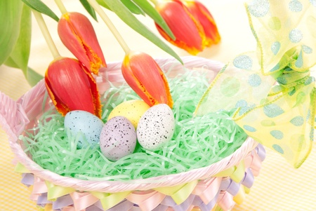 Easter spring eggs in basket and tulip flowers photo