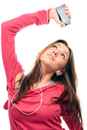 Young girl listening, enjoying music and holding cellular mp3 player in earphones on top of her head wearing dance pink top, isolated on white background photo