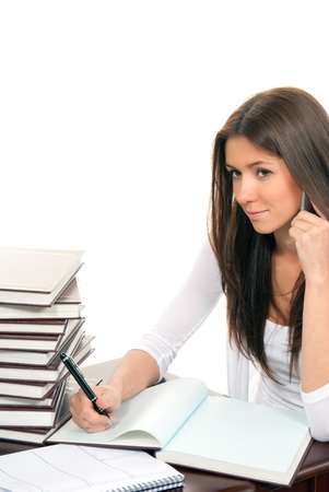 Brunette Business woman sitting in an office writing and talking on mobile phone with a pen in the hand offer to sign contract, on the table books, paper and notebook isolated on a white background photo
