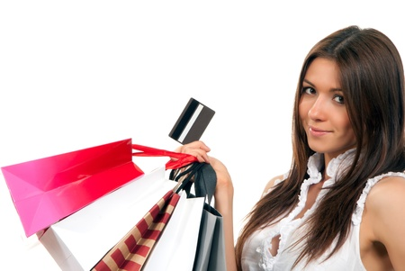 Pretty young woman with shopping bags, credit gift card in one hand buying presents, smiling and looking at the camera isolated on a white background Stock Photo - 9057257
