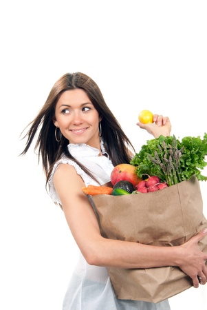 mercearia: Happy young woman holding a shopping bag full of groceries, mango, salad, asparagus, radish, avocado, lemon, carrots on white background