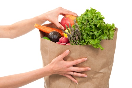 Hands holding a shopping paper bag full of groceries, one hand pick out ripe mango, avocado, asparagus, carrots, radish, lime and lemon on a white background photo
