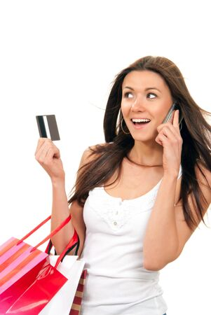 Happy Beautiful woman with shopping bags and credit gift card talking on cellular mobile phone, cheerful smiling on a white background Stock Photo - 9057262