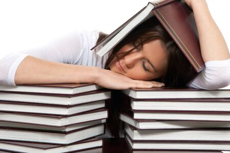 Pretty young girl is lying on the table under stacks of books, over textbooks  on a white background  photo