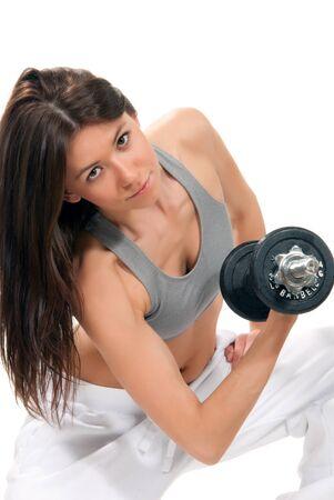 Mujer de aptitud bastante morena con perfecto entrenamiento Atlético de cuerpo y abs con pesos de levantamiento de pesas aislados en un fondo blanco photo