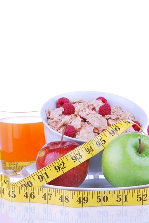 Diet concept with tape measure red and organic green apple, corn healthy corn flakes with fresh raspberries and carrot juice on a white background Stock Photo - 9137513