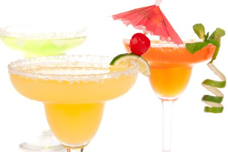 rimmed: Yellow margarita cocktails in chilled salt rimmed glasses with tequila, triple sec, juice, simple syrup and crushed ice garnished slice of fresh lime in margaritas glass isolated on white background Stock Photo