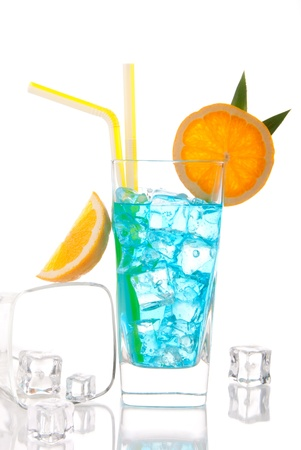 Blue hawaiian  lagoon curacao cocktail decorated with pineapple leaf, orange slice and cocktails straw and glass filled with ice isolated on a white background photo