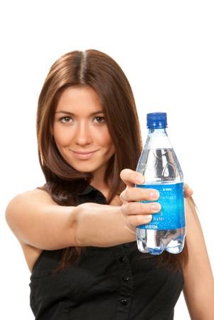 purified water: Chica ofrecer y dar botella de agua potable todav�a para la dieta. Mujeres sosteniendo en mano espumoso mineral embotellada agua aislado en un fondo blanco Foto de archivo