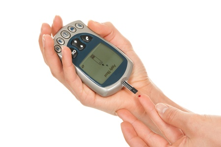 Diabetes measurement glucose sugar level blood test for diabetic patient using new smart glucometer test isolated on a white background photo