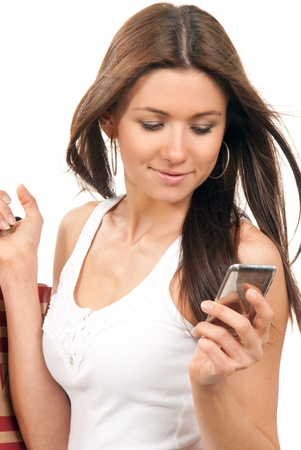 Pretty smiling girl reading texting a message on the cellphone mobile and holding shopping bags in hands on a white background photo