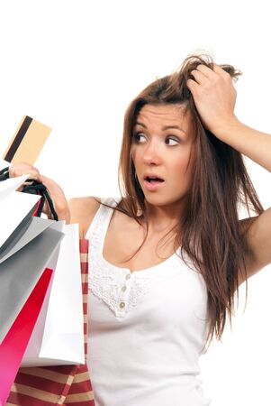 Attractive beautiful woman holding credit gift card and paper shopping bags with a surprised and shocked expression on her face on a white background photo