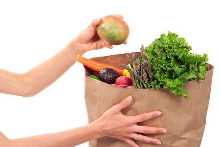 Hands holding a shopping paper bag full of groceries, one hand taking out ripe mango, avocado, asparagus, carrots, radish, lime and lemon on a white background Stock Photo - 9168003