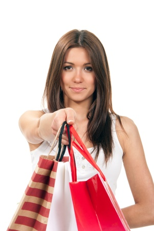 Young attractive cheerful smiling girl holding offer colored paper shopping bags in hand and giving them to the camera on a white background. Focus on face photo