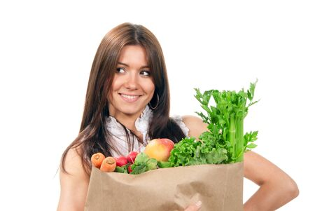 supermarket: Pretty young woman holding a grocery shopping  bag with mango, carrot, radish, salad, lettuce and smiling on a white background