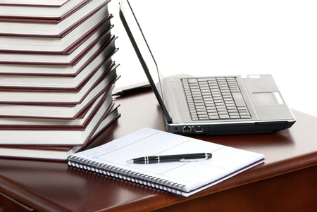 Work place table with stacks of real books on it and modern lap top, pen and textbook lying near on a white background. photo