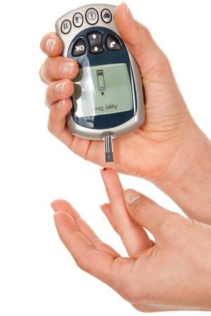 diabetes: Dedo poked paciente de diabetes para medir una prueba de nivel de glucosa en sangre por nuevo gluc�metro inteligente aislado en un fondo blanco