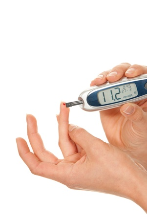 Diabet patient measuring glucose level blood using glucometer test isolated on a white background. High blood sugar hyperglycemia photo
