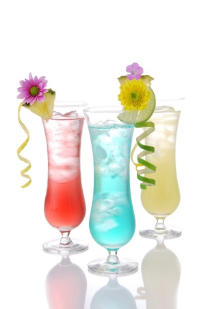 alcoholic drinks: Cocktails margarita martini row with vodka, light rum, gin, tequila, blue curacao, lime juice, lemonade, lemon slice and fresh summer flowers in martinis cocktail glass on a white background Stock Photo