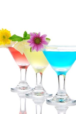 Cocktails martini row with vodka, light rum, gin, tequila, blue curacao, lime juice, lemonade, lemon slice and fresh summer flowers in martinis cocktail glass on a white background Stock Photo - 9195887