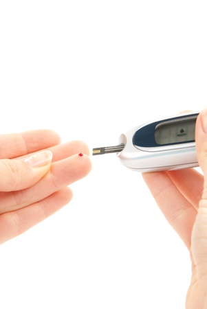 dependent: Dependent first type Diabetic patient measuring glucose level blood test using ultra mini glucometer and small drop of blood from finger and test strips isolated on a white background