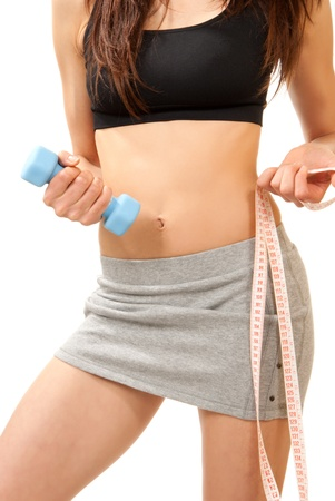 Diet weight loss concept woman perfect body abs breast and legs with tape measure and small jogging blue dumbbells on a white background photo