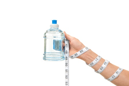 Diabetes diet concept tape measure twisted around woman hand, wrist and measuring blue bottle of drinking sparkling mineral water on a white background photo