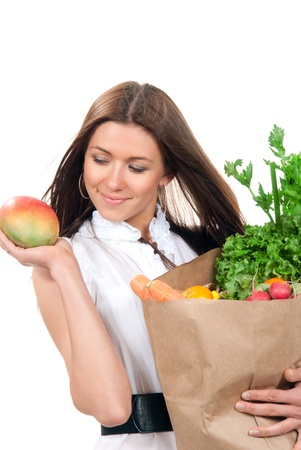 Happy young woman holding a shopping bag full of vegetarian groceries, mango in hand, salad, asparagus, radish, avocado, lemon, carrots, oranges isolated on white background Stock Photo - 9277534