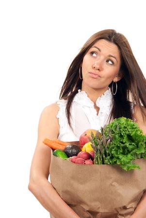 Gelukkig jonge vrouw met een boodschappentas vol vegetarisch boodschappen, mango, salade, asperges, radijs, avocado, citroen, wortelen, sinaasappelen en denken geïsoleerd op witte achtergrond