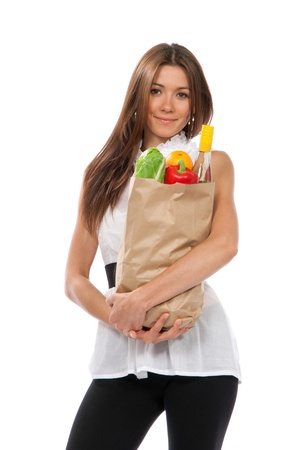 Young woman hold shopping paper bag full of vegetarian groceries, red pepper, salad, bottle of dry wine, orange  isolated on white background  photo