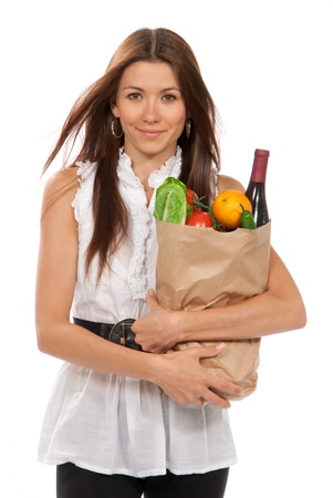 Pretty young woman holding a shopping bag full of vegetarian groceries, tomatoes, salad, bottle of red wine, orange, pepper isolated on white background