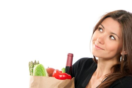 grocer: Young woman hold shopping paper bag full of vegetarian groceries, red pepper, salad, bottle of dry wine, mango isolated on white background. Close-up composition