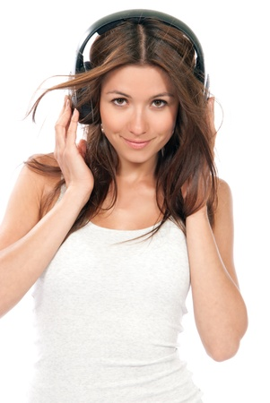 Happy brunette slim woman listening and enjoying music in headphones, smiling, laughing and not looking in camera isolated on a white background photo