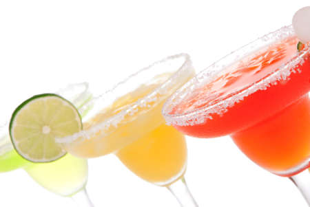 alcoholic beverages: Strawberry, lime, apple Margaritas cocktails composition decorated with twisted lime, mint, cherry, cocktail umbrella in margarita glass isolated on a white background