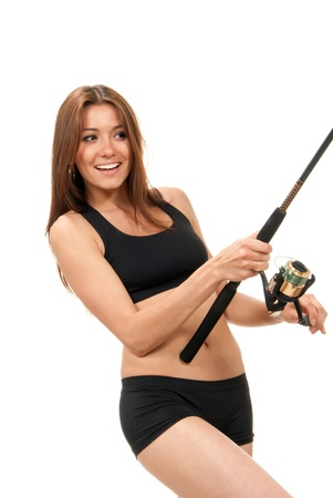 fishing pole: Pretty fisher woman standing, holding fishing pole with a reel in hands, catching fish, smiling on a white background