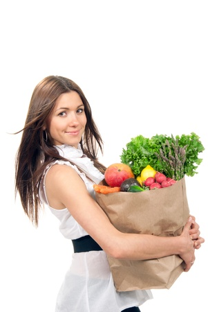 Happy young woman holding a paper shopping bag full of groceries, mango, salad, asparagus, radish, avocado, lemon, carrots on white background photo