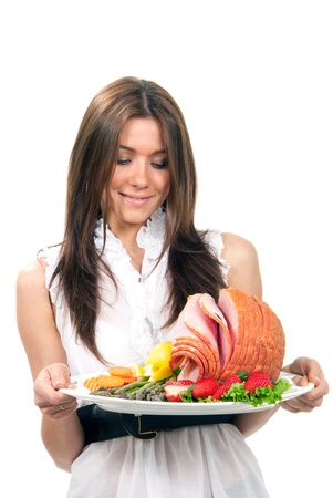 turkey bacon: Pretty chef woman holding a plate in hand with turkey meat ham with lettuce, asparagus, carrot, strawberry and lemon on a white background