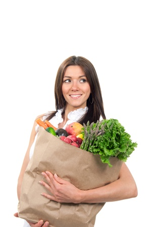 Pretty woman mother smiling and holding supermarket shopping paper bags full of vegetables: mango, asparagus, lettuce, radish, carrot in her hands on a white background