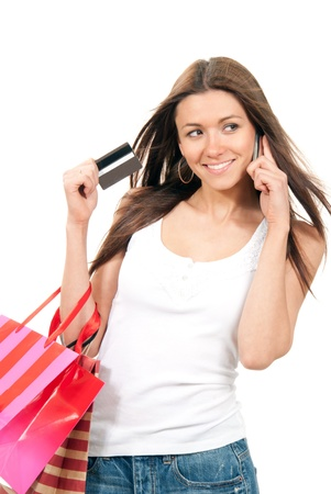 Beautiful ecstatic woman holding shopping bags and credit gift-card in hand, talking by cell phone mobile on a white background photo