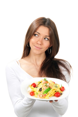 Young woman chef holding the plate with italian lemon pappardelle, tagliatelle, macaroni, spaghetti pasta with tomato, shrimps and olives on it in hand on a white background. Focus on Pasta plate