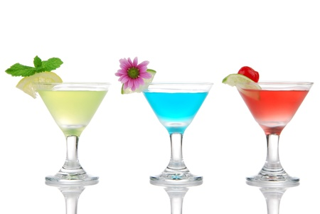 Tropical martini Cocktails row with vodka, light rum, gin, tequila, blue curacao, lime juice, lemonade, lemon slice and fresh summer flowers in martinis cocktail glass on a white background