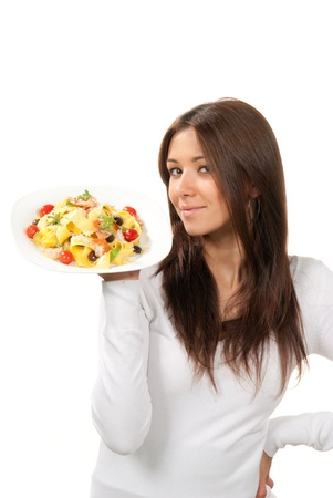 Young woman chef holding the plate with italian lemon pappardelle, tagliatelle, macaroni, spaghetti pasta with tomato, shrimps and olives on it in hand on a white background. Healthy food concept photo
