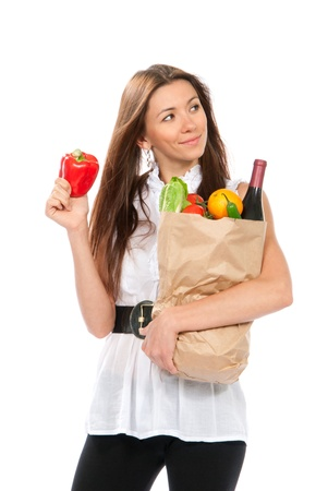 Happy young woman holding a shopping bag full of groceries, mango, salad, red papper, radish, tomato, orange, bottle of wine on white background  photo